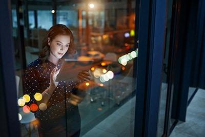 Femme debout derrière une vitre d'une tour d'un quartier d'affaires, travaillant sur une tablette numérique