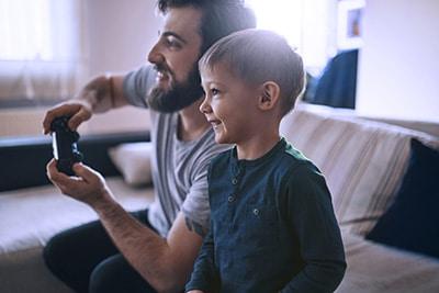 Un père et son jeune fils (4 ans) assis dans un canapé jouant aux jeux videos